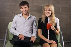 Young man and woman sitting with a laptop Royalty Free Stock Images