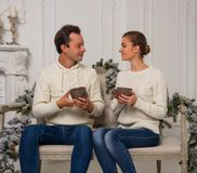 Young man and woman are sitting and looking at each other on a c. Young men and women are sitting and looking at each other on a couch in a room with Christmas Royalty Free Stock Photo