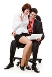 Young man and woman sitting, looking at laptop. Young man and woman sitting in a chair, looking at laptop, isolated on a white background Royalty Free Stock Photography