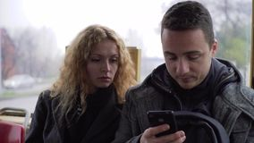 Young man and woman sitting in tram chatting about gadgets and sharing something online.  stock video footage
