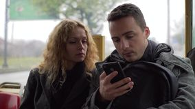 Young man and woman sitting in tram chatting about gadgets and sharing something online.  stock video