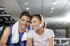 Young man and woman smiling and sitting together at the gym. Young men and women couple smiling and sitting together at the gym during a workout Stock Photo