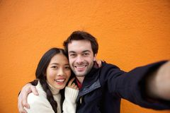 Young man and woman smiling while taking selfie Royalty Free Stock Photos