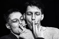 Young man and woman smoking cigarettes Royalty Free Stock Images