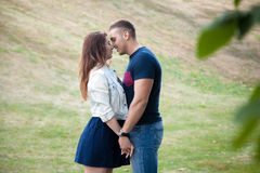 Young man and woman snuggling in park Stock Images