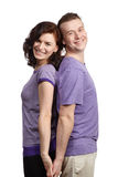 Young man and woman stand back to back. And holding each other's hands Royalty Free Stock Image