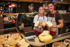 Young man and woman stand at cheese shelf in grocery store. Happy positive workers pose on camera and smile. Cheese. Paradise royalty free stock images