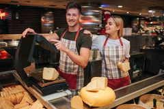 Young man and woman stand at cheese shelf in grocery store. He weight cheese. Female model lean to guy look at him and. Young men and women stand at cheese shelf stock images
