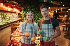 Young man and woman stand at fruit boxes in grocery store. They hold oranges and apples in hands. Workers look straight. And pose on camera royalty free stock photo