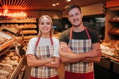 Young man and woman stand in grocery store together. They hold hands crossed and pose on camera. People smile. Positive. Happy workers royalty free stock image