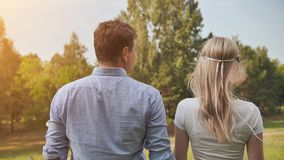 Young man and woman stand with their backs in the park stock video footage