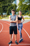 Young man and woman standing on athletics race track. Full length shot of young men and women standing on athletics race track at the stadium Stock Images