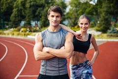 Young man and woman standing on athletics race track. Full length shot of young men and women standing on athletics race track at the stadium Royalty Free Stock Photography