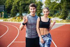 Young man and woman standing on athletics race track. Full length shot of young men and women standing on athletics race track at the stadium showing v sign and Stock Image