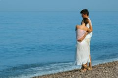 Young man and woman standing on the beach Stock Photos