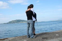 Young man and woman standing at the shore and looking at the sea Stock Image