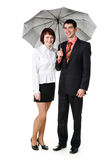 Young man and woman standing under an umbrella. Young man and woman standing under an umbrella, isolated on a white background Royalty Free Stock Photography