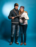 Young man and woman standing in warm clothes and tying one scarf Stock Images