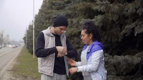 Young couple looks on their fitness trackers and compares the time