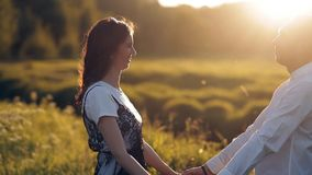 Young man and woman strolling in a meadow at sunset in summer. Romance. Summer love togetherness joy romantic memories. Forever together concept stock footage