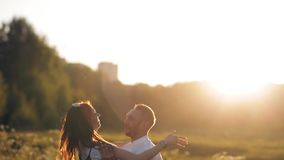 Young man and woman strolling in a meadow at sunset in summer. Romance. Summer love togetherness joy romantic memories. Forever together concept stock video