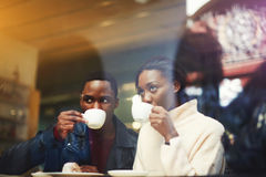 Young man and woman students drinking hot beverages while resting after lectures in University Royalty Free Stock Photos
