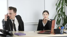 Young man and woman in suits are talking in the office, the man is distracted by a telephone conversation. Office