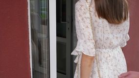 Man and woman come into cozy cafe closeup slow motion. Young man and woman in summer clothes come into cozy cafe with glass door close view slow motion stock video footage