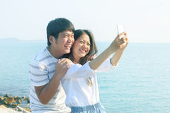 Young man and woman take a photo by smart phone at sea side use Stock Images