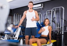 Young man and woman taking pause between exercising in gym Royalty Free Stock Image