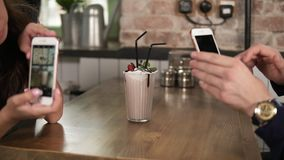 Young man and woman taking picture of a glass with milk shake with cherry on the top and straw on a wooden table in cafe stock footage