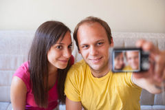 Young man and woman taking self portrait Stock Images