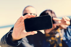 Young man and woman taking a selfie with a smartphone Royalty Free Stock Photography