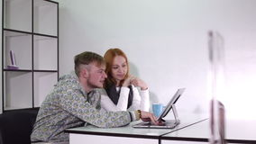 Young man and woman talking with different emotions. Two people have a conversation in the office sitting at the table.On the table is a laptop stock video footage