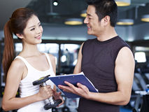Young man and woman talking in gym Stock Images