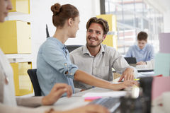 Young man and woman talking in an�open plan office Royalty Free Stock Images