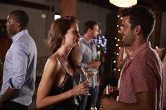 Young man and woman talking at a party, side view royalty free stock images