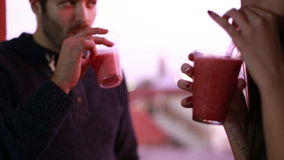 Young man and woman toasting and drinking fruit smoothie