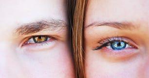 Young man and woman together, close up, eyes, stare. A young men and a women together, close up, eye to eye, staring at a camera Royalty Free Stock Images