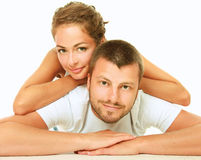 Young man and woman together over white background. Happy couple lying on floor and smiling at camera isolated on white background Royalty Free Stock Photography