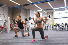 Young man and woman training with barbell in gym Royalty Free Stock Photo