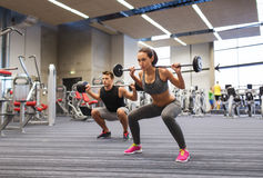 Young man and woman training with barbell in gym Stock Image