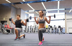 Young man and woman training with barbell in gym Stock Photo