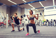 Young man and woman training with barbell in gym Royalty Free Stock Photography