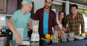 Young Man And Woman Use Blender Prepare Healthy Smoothie Pour It In Glasses People Group Talking Two Couples In Kitchen stock video footage