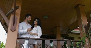 Young man and woman use cell smart phone on balcony in hotel, happy smiling couple embracing surfing internet together stock video footage