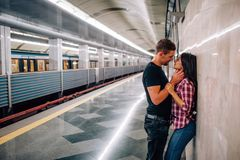 Young man and woman use underground. Couple in subway. Cheerful paasionate people lean to wall. kissing time. Guy hold. Young men and women use underground royalty free stock photo