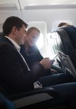 Young man and woman using cell phone in plane Royalty Free Stock Photo