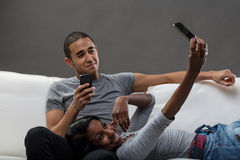 Young man and a woman using mobile phones Royalty Free Stock Photography
