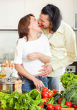 Young man and woman with vegetables in kitchen Royalty Free Stock Photography